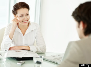Cute young business woman taking an interview of a man