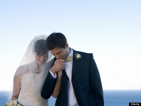 A groom kissing his bride's hand. Image shot 2007. Exact date unknown.