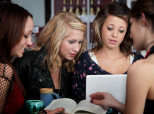 Four young female students study at a cafe