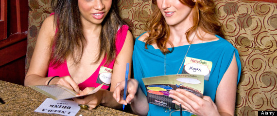 Female speed dating participants read an evaluation form of male participants at a California restaurant.. Image shot 2011. Exact date unknown.